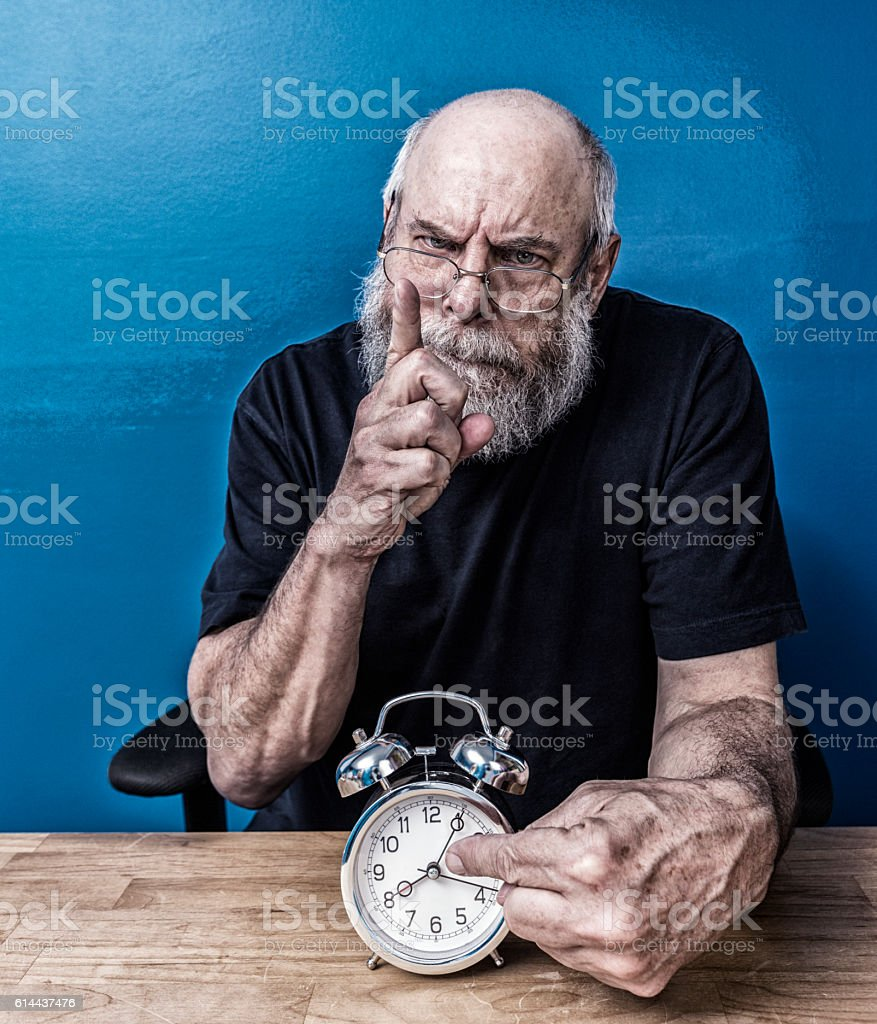 Angry Blue Collar Boss Pointing At Late For Work Clock stock photo