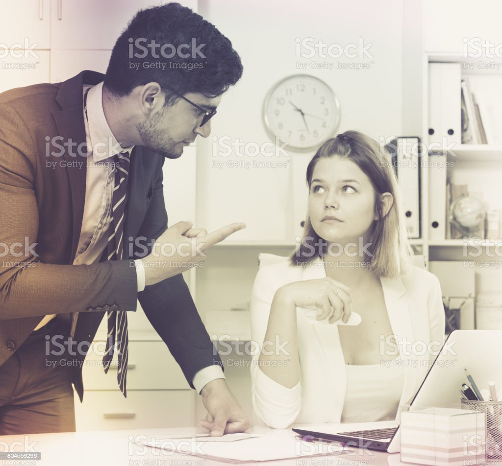 Angry boss blowing up female stock photo