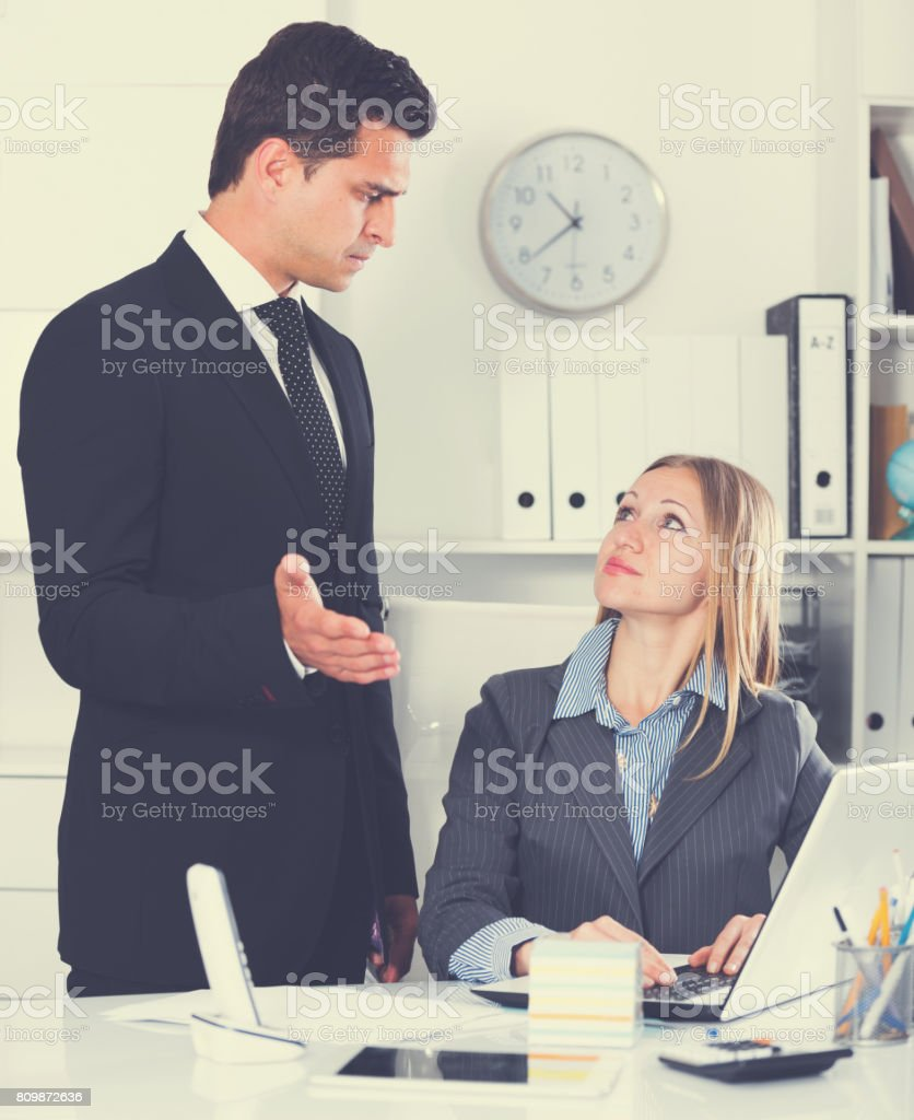 Angry boss blowing up subordinate stock photo