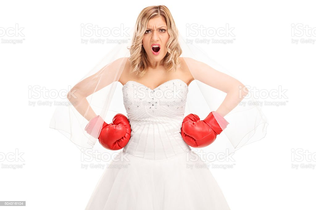 Angry bride in a wedding dress and boxing gloves stock photo