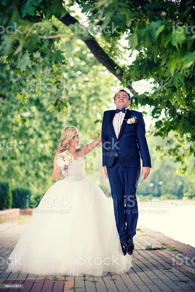 Angry Bride with one Hand holding the Groom in Air stock photo