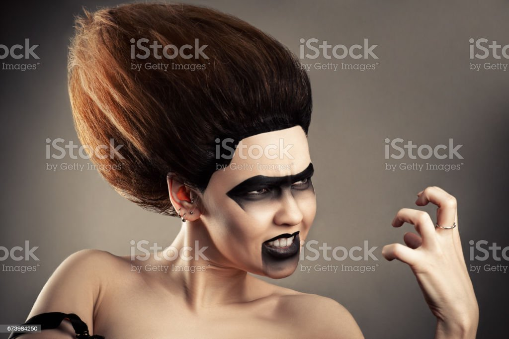 angry brunette woman with dark makeup and lush hairdo stock photo