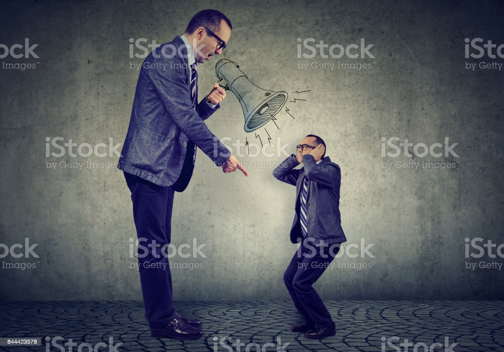 Angry business man boss screaming at himself small in megaphone stock photo