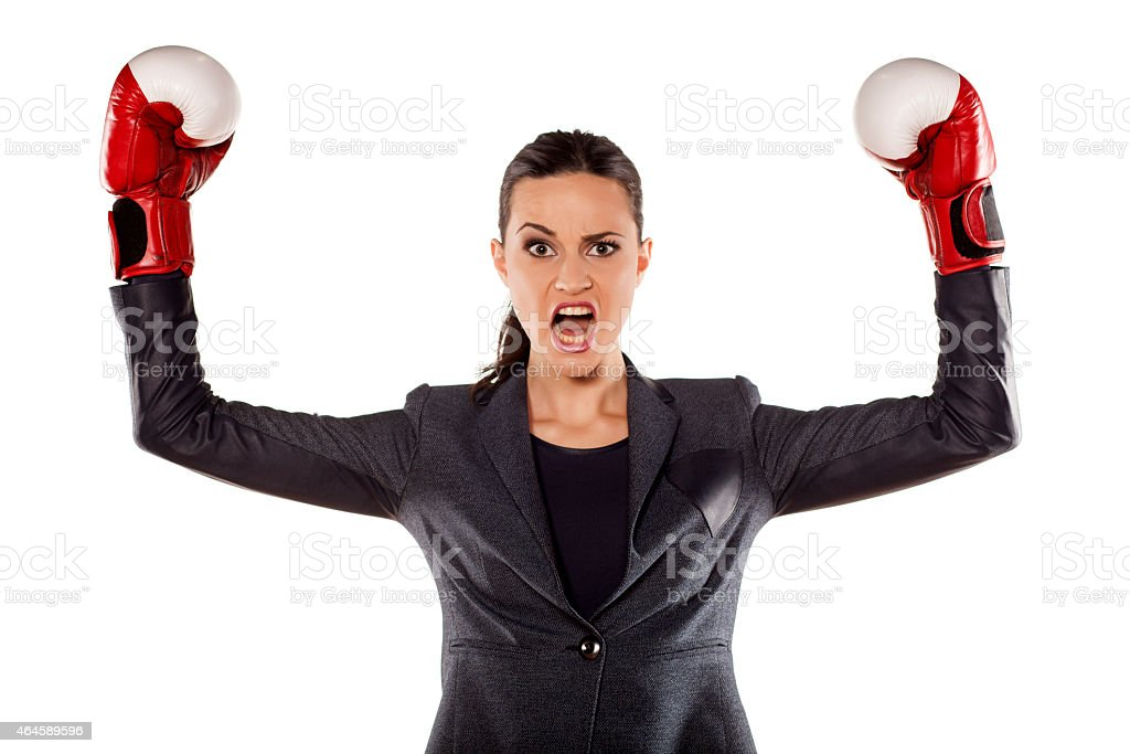 Angry business woman with boxing gloves in winning position stock photo