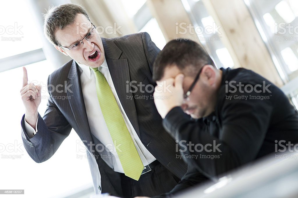 Angry businessman and his subordinate stock photo