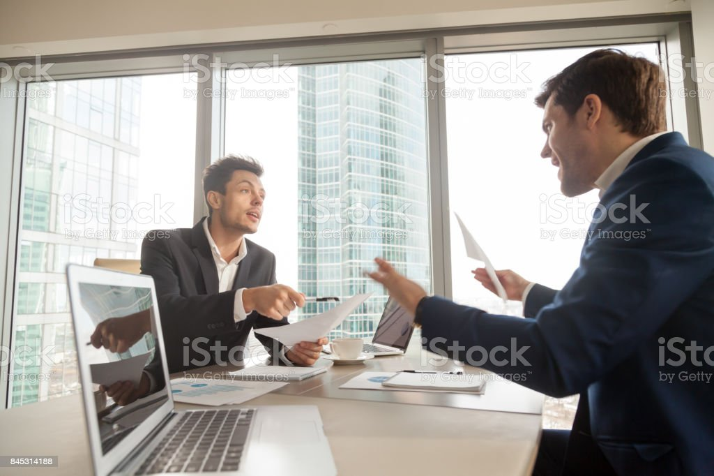 Angry businessman arguing with partner on meeting stock photo