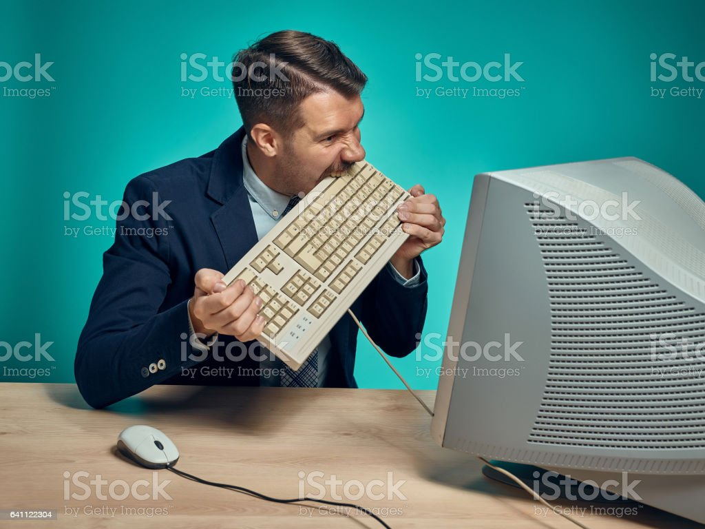 Angry businessman breaking keyboard against blue background stock photo