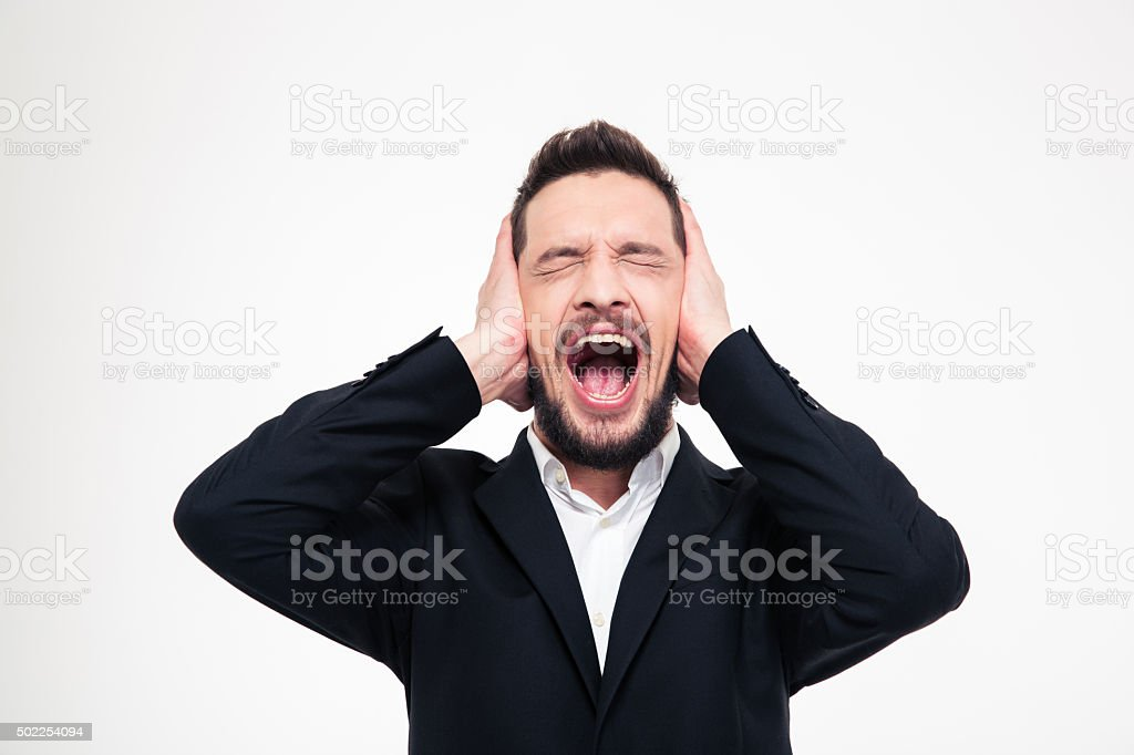 Angry businessman covering his ears and screaming stock photo