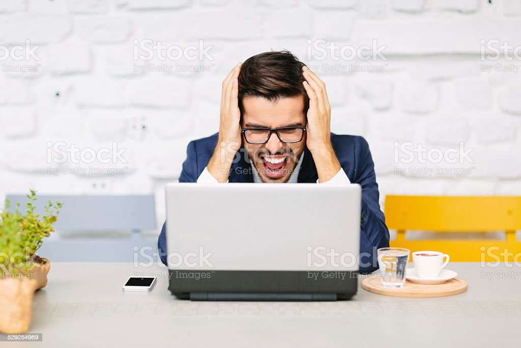 Angry businessman holding his head stock photo