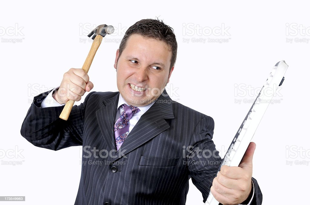 Angry Businessman is breaking the keyboard with hammer royalty-free stock photo