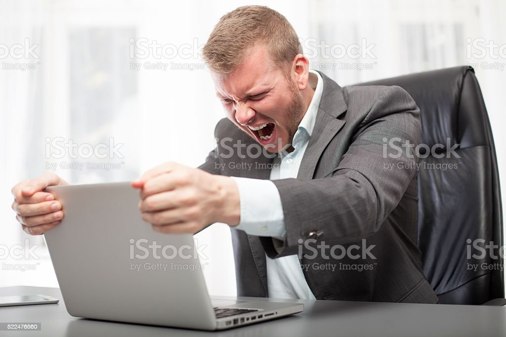 Angry businessman shaking his laptop computer stock photo