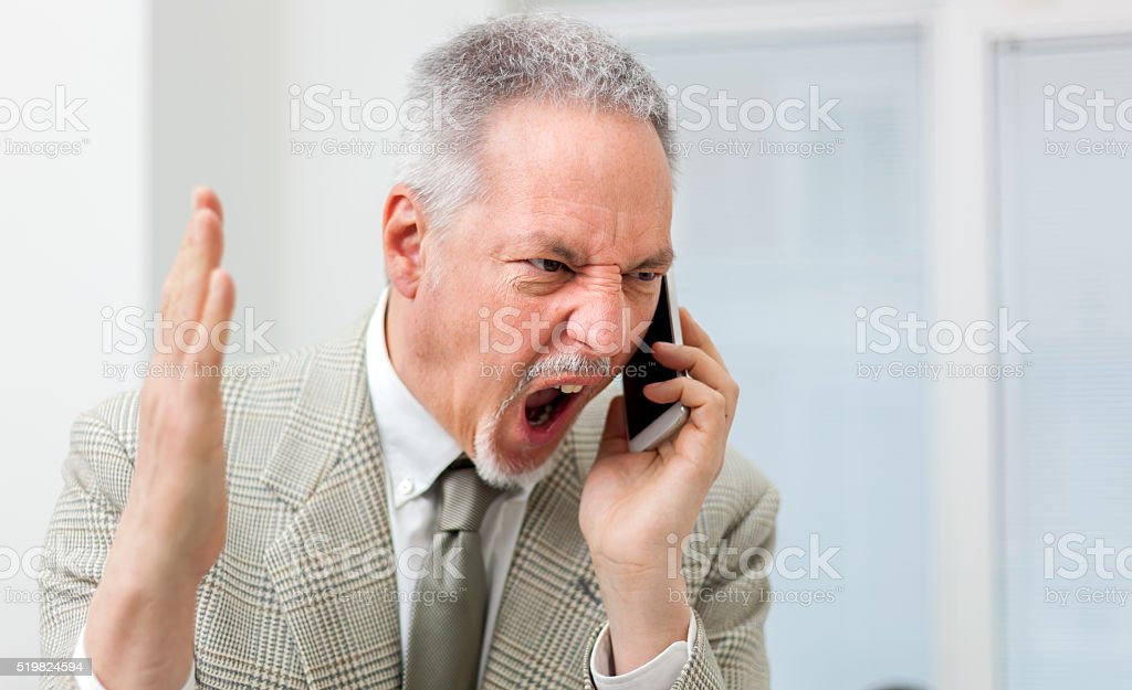 Angry businessman shouting on the phone stock photo