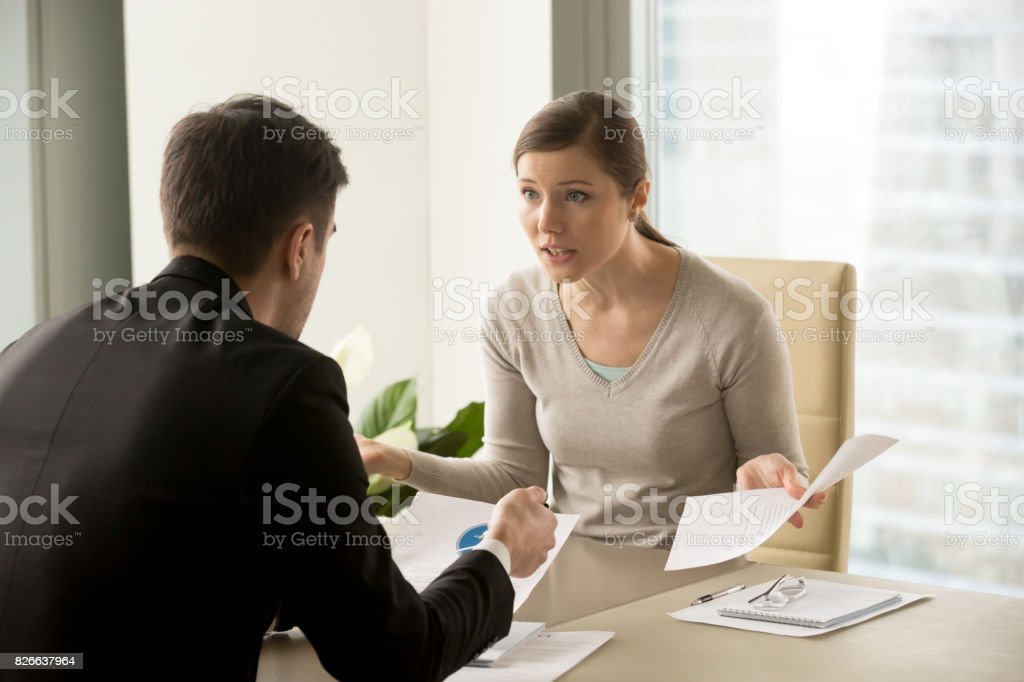 Angry businesswoman arguing with businessman about paperwork failure at workplace stock photo