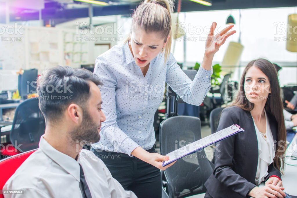 Angry businesswoman shouting to a stressed employee at office. stock photo