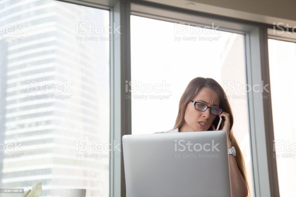 Angry businesswoman talking on mobile at workplace, arguing by cell stock photo