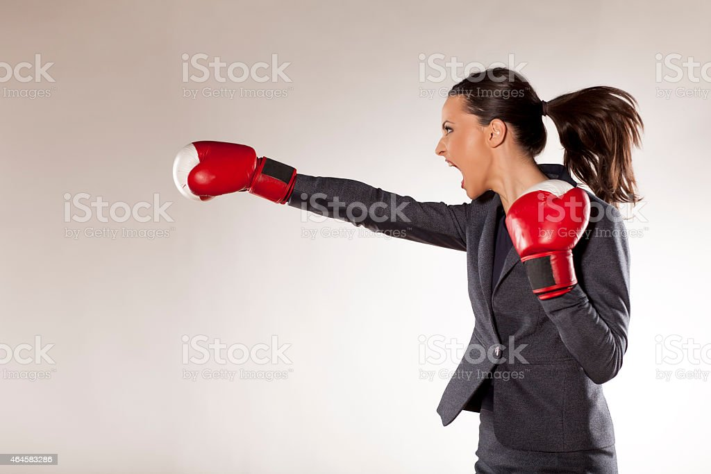 Angry businesswoman with red boxing gloves giving a punch stock photo