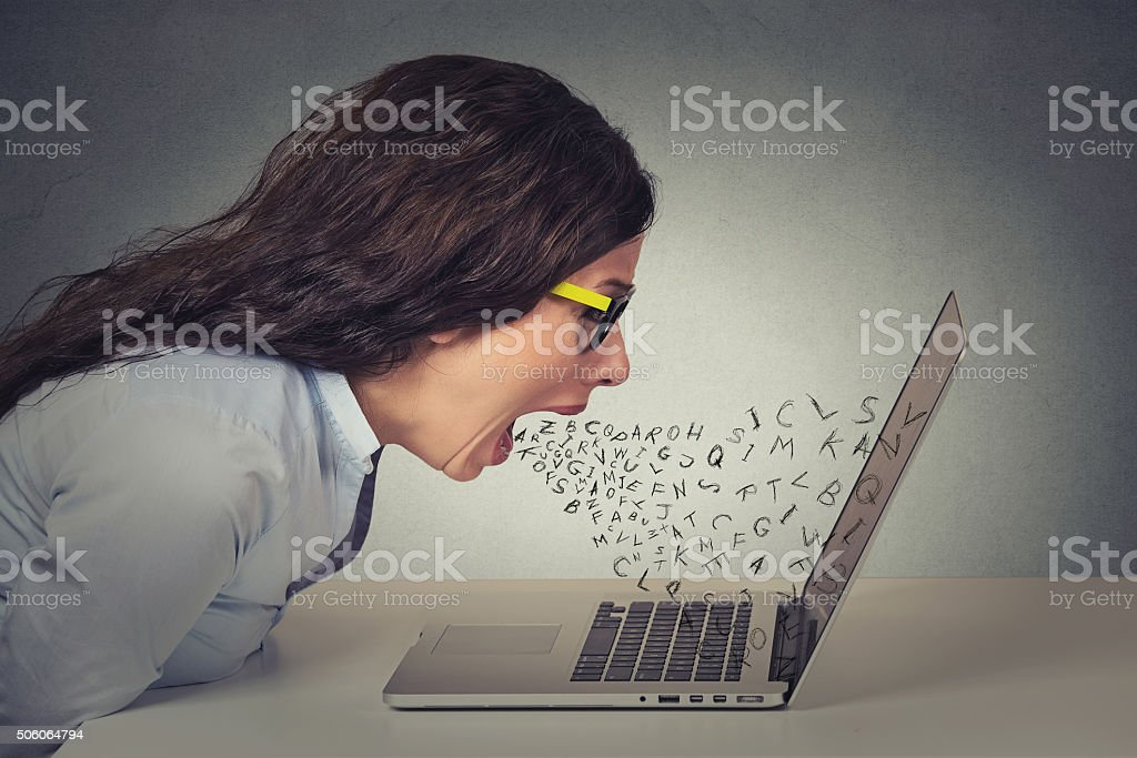 Angry businesswoman working on computer, screaming stock photo