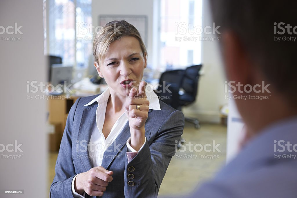 A angry businesswoman yelling at a male colleague stock photo