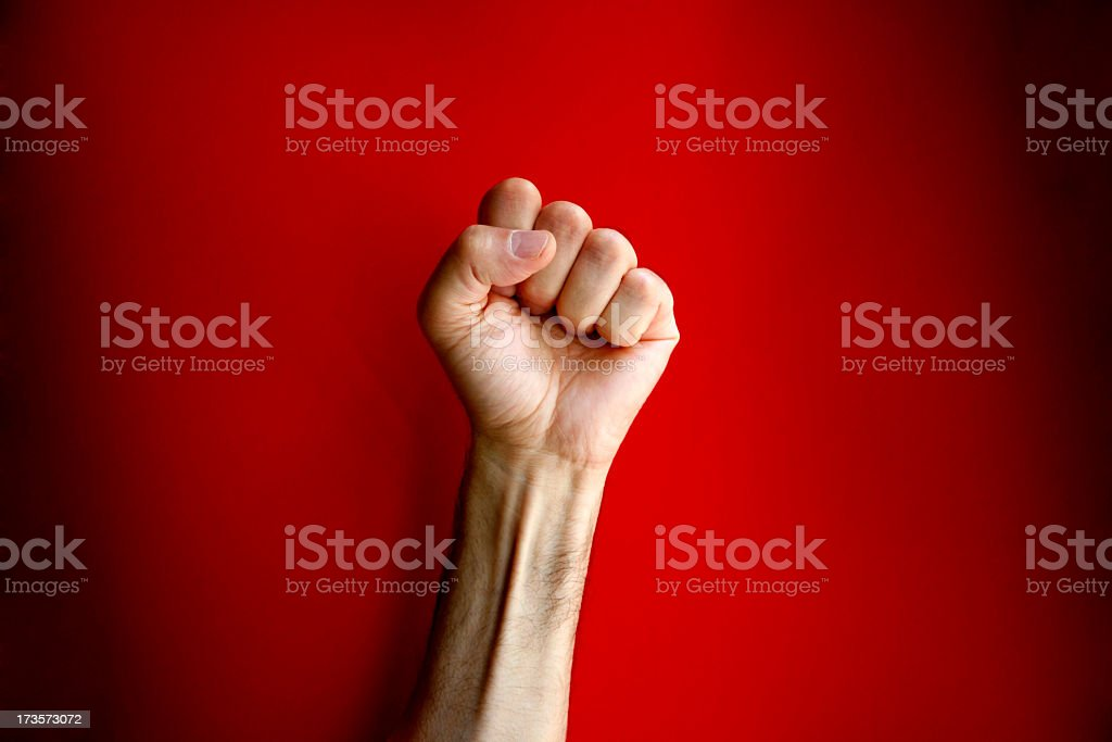 Angry clenched fist on red background stock photo