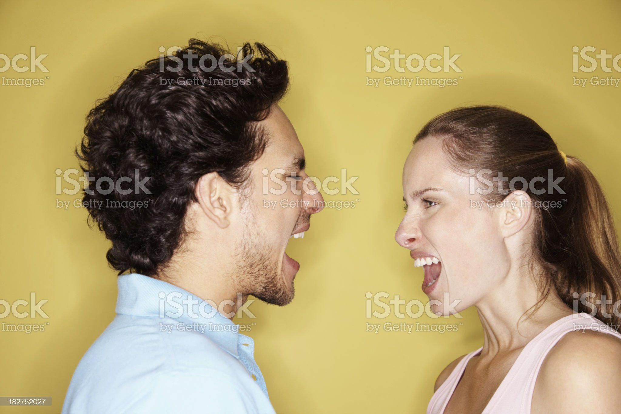 Angry couple yelling at each other against yellow background royalty-free stock photo