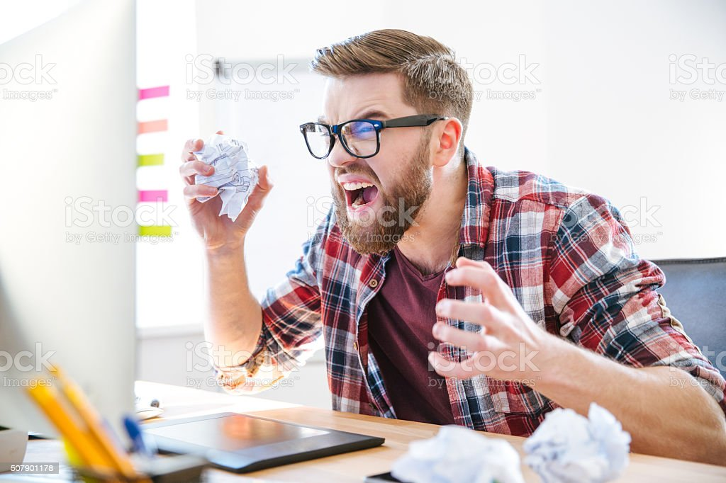 Angry crazy designer yelling and crumpling paper on his workplace stock photo
