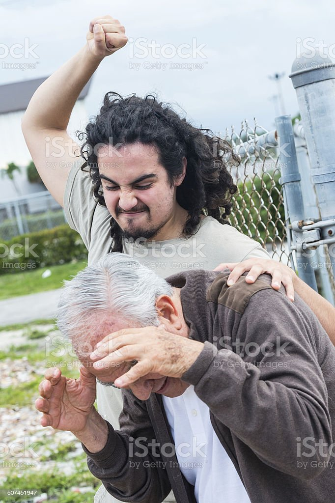 Angry dark haired man assaulting elderly man stock photo