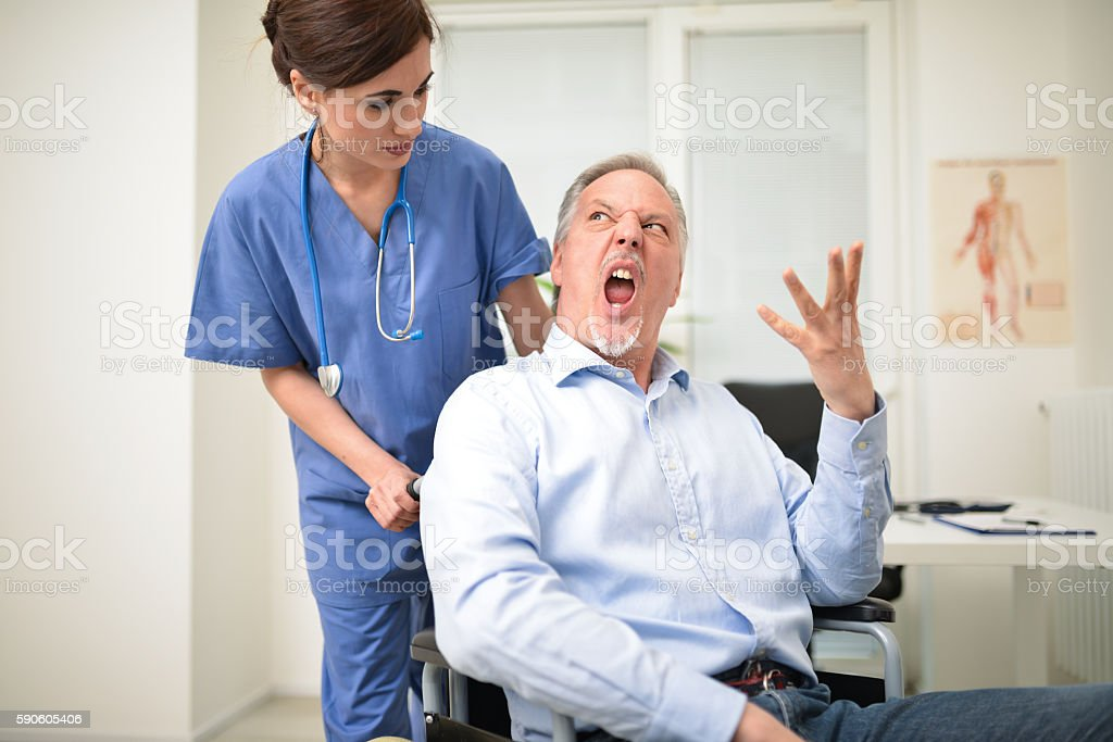 Angry disabled patient and a nurse stock photo