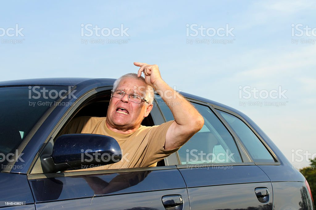 Angry driver leaning out of his car window stock photo