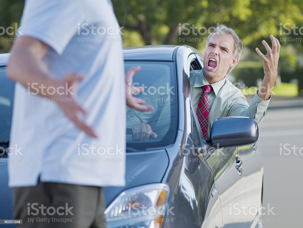 Angry driver shouting at pedestrian blocking road stock photo