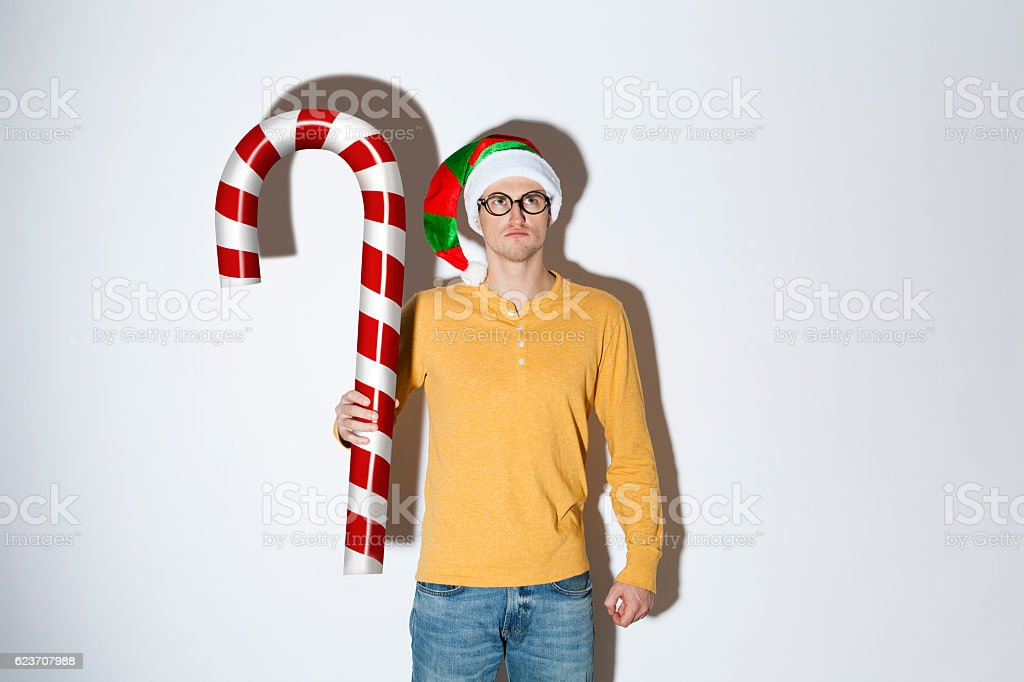 Angry elf holding a huge candy cane stock photo