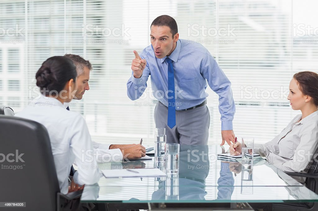 Angry executive pointing out his employee stock photo