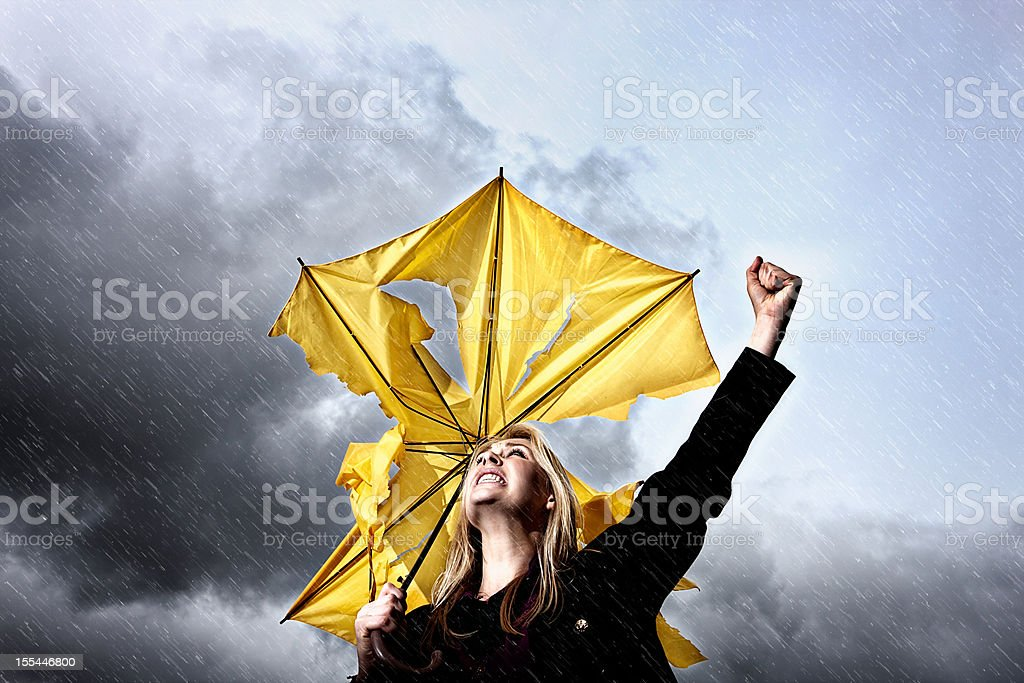 Angry, frustrated woman with broken umbrella shaking fist at thunderstorm stock photo