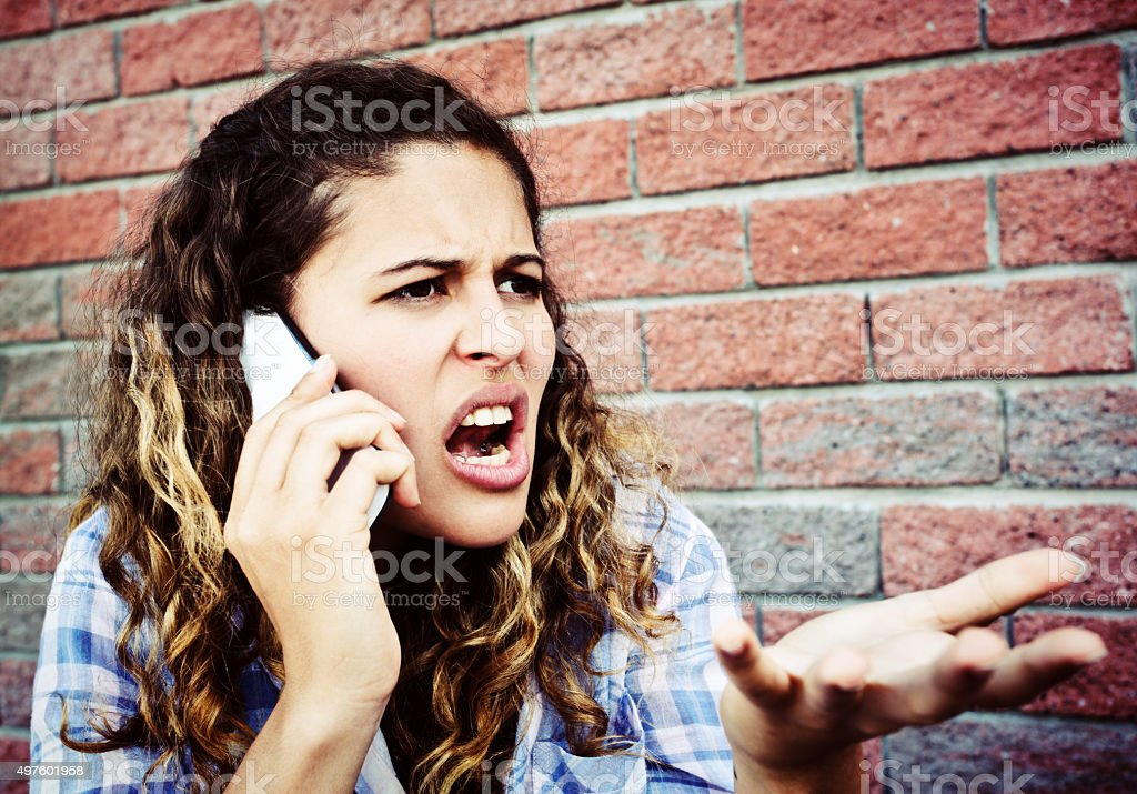 Angry, frustrated  young woman shouts into her cellphone, gesturing angrily stock photo