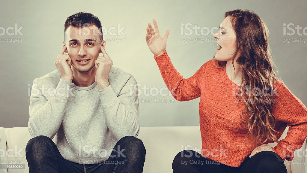 Angry fury woman screaming man closes his ears. stock photo
