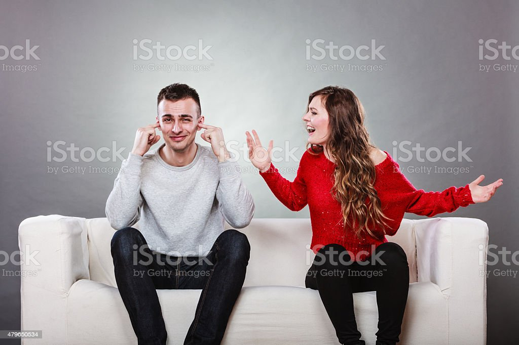 Angry fury woman screaming man closes his ears. stock photo