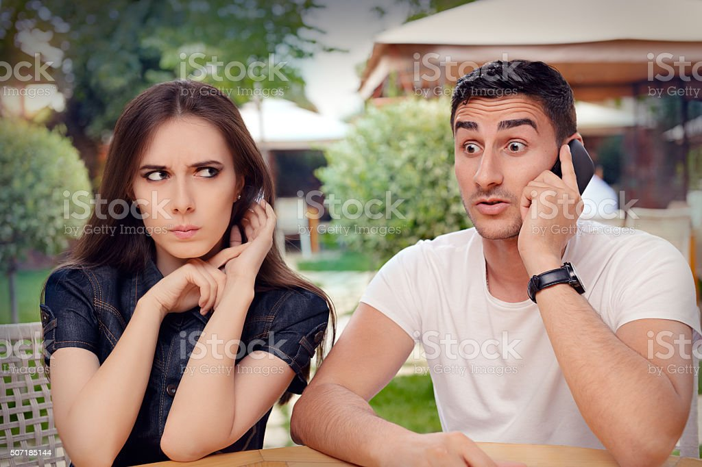 Angry Girl Listening to Her Boyfriend Talking on The Phone stock photo