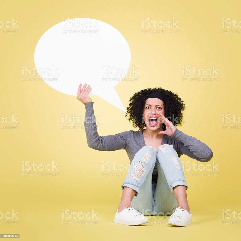 Angry girl screaming and holding empty speech balloon. stock photo