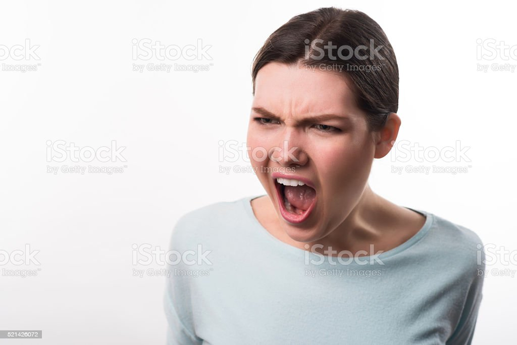 Angry girl standing isolated on white background stock photo