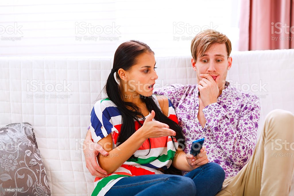 Angry girl with mobile and looking on confused boyfriend royalty-free stock photo