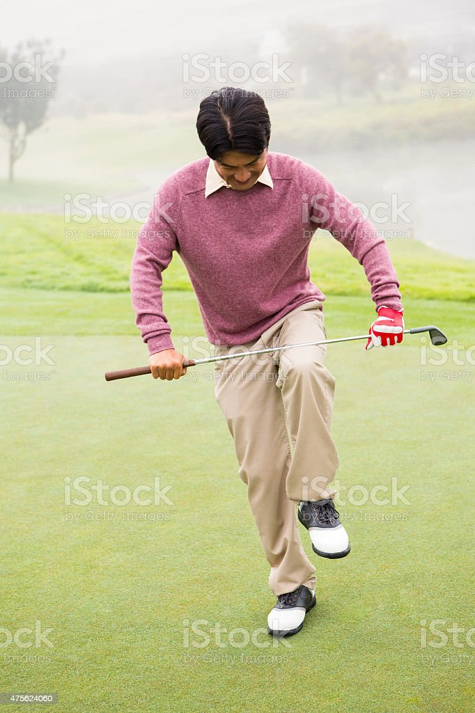 Angry golfer trying to brake his club stock photo
