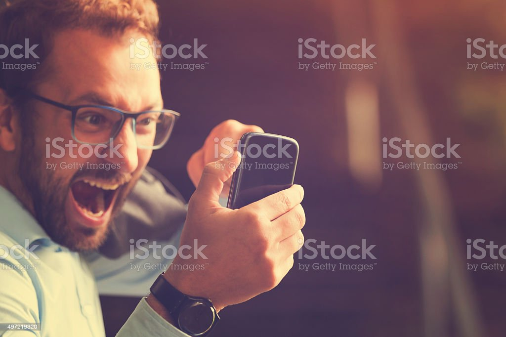 Angry guy biting the phone. stock photo