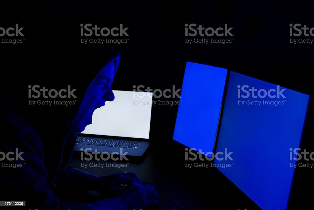 angry hacker in front of blue screen royalty-free stock photo