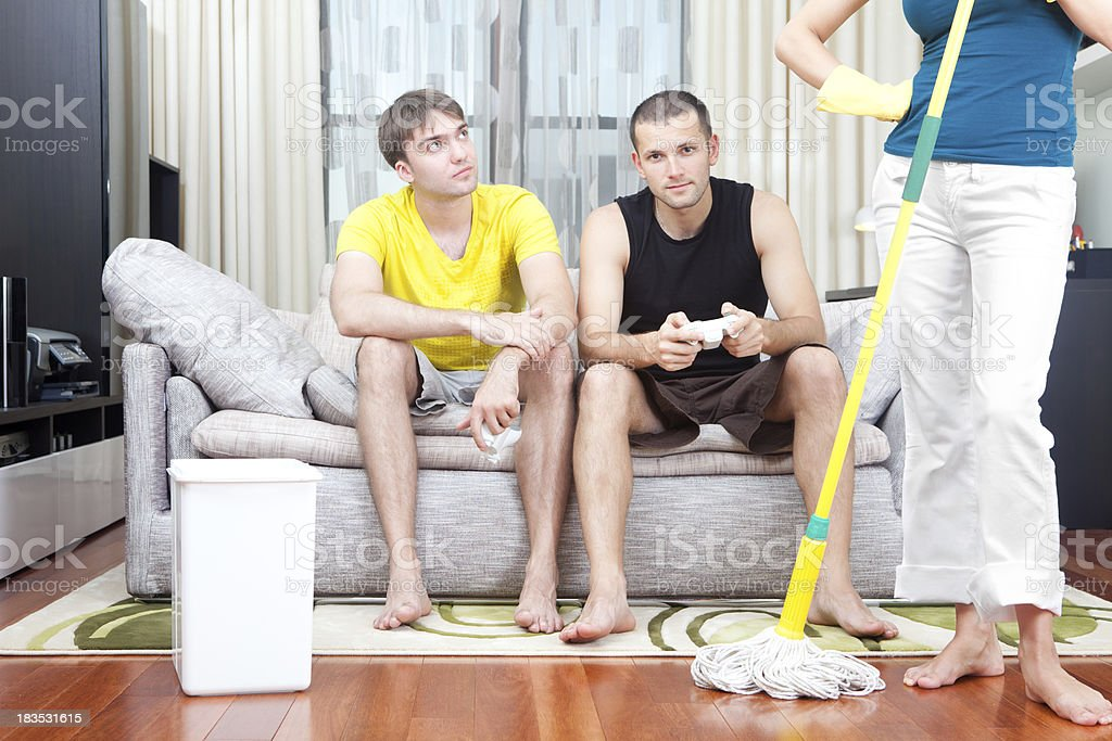 Angry housewife cleaning while two guys playing games stock photo