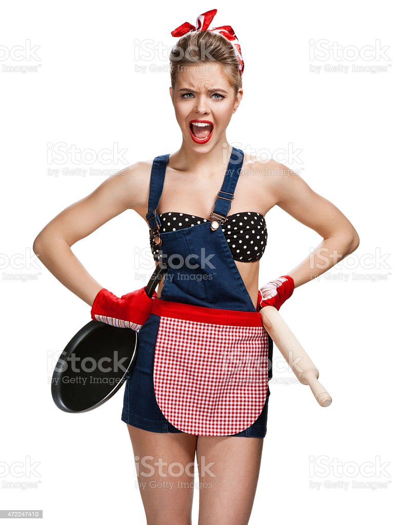 Angry housewife with battledore and black frying pan stock photo