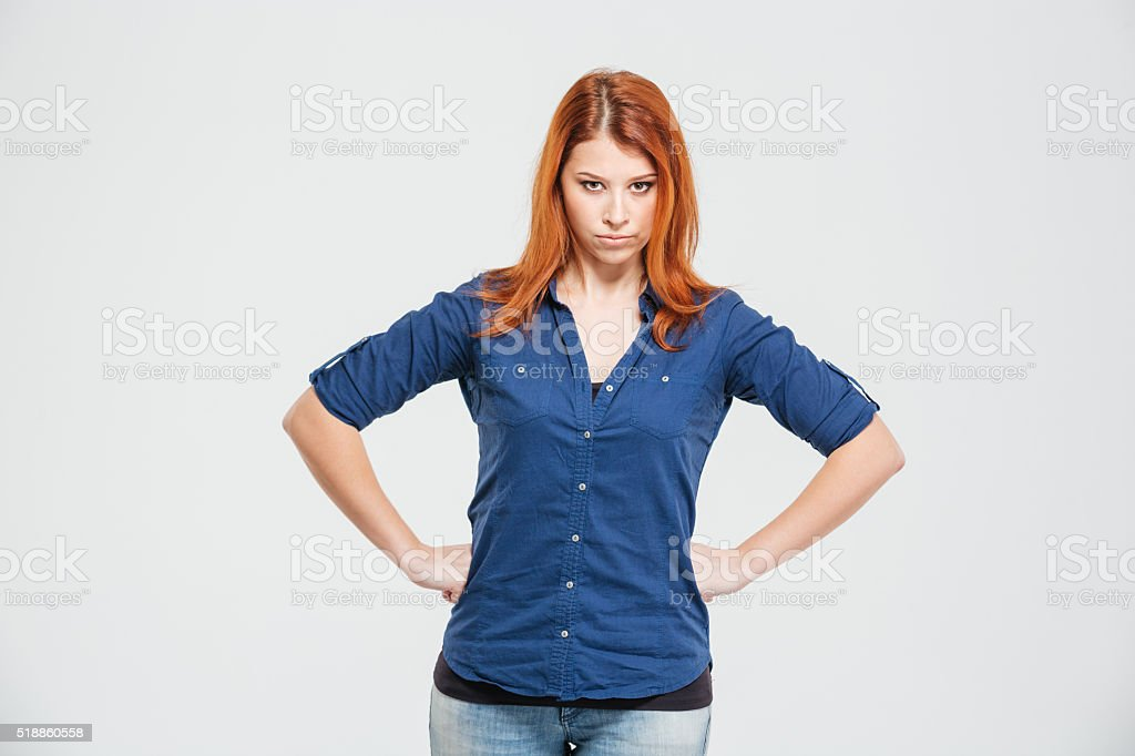 Angry irritated redhead young woman standing with hands on waist stock photo
