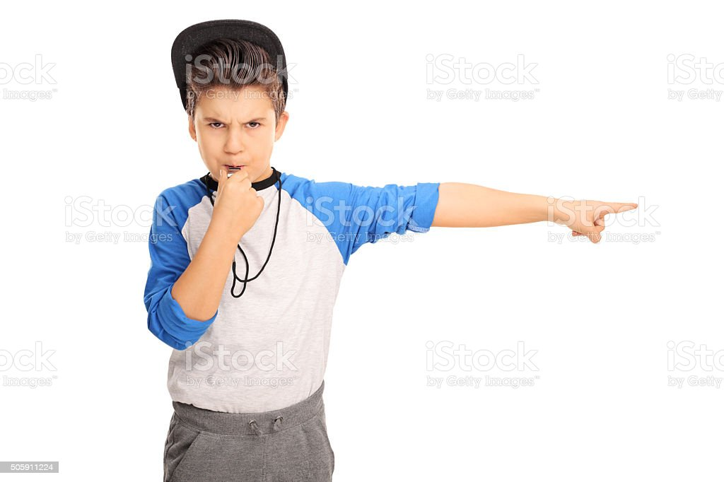 Angry kid blowing a whistle and pointing stock photo
