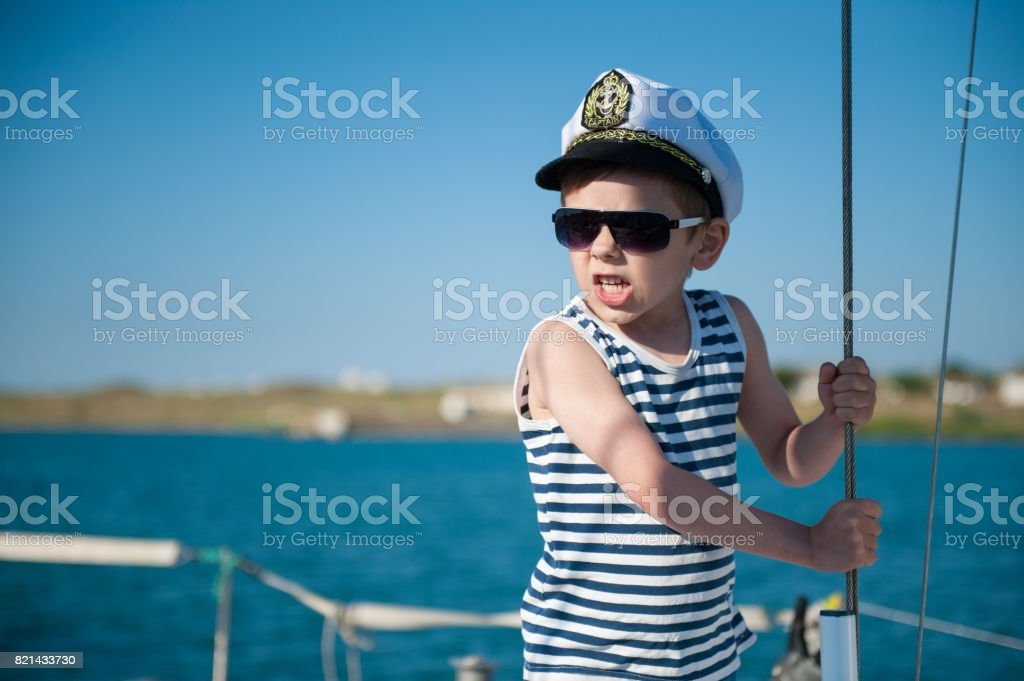angry little boy captain shouting orders aboard vessel stock photo