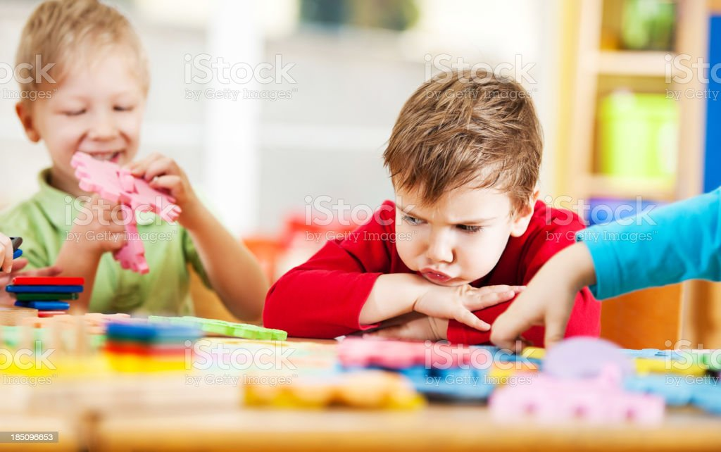Angry little boy looking at puzzles. stock photo
