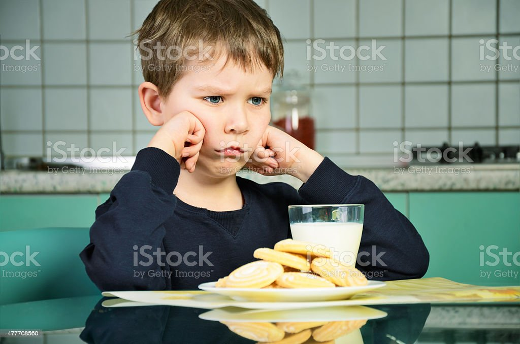 Angry little boy sitting at the dinner table. horizontal stock photo