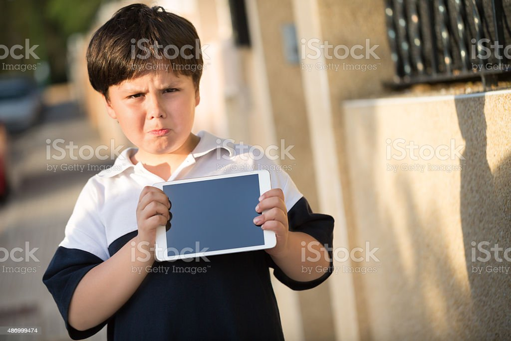 angry little boy with digital tablet stock photo